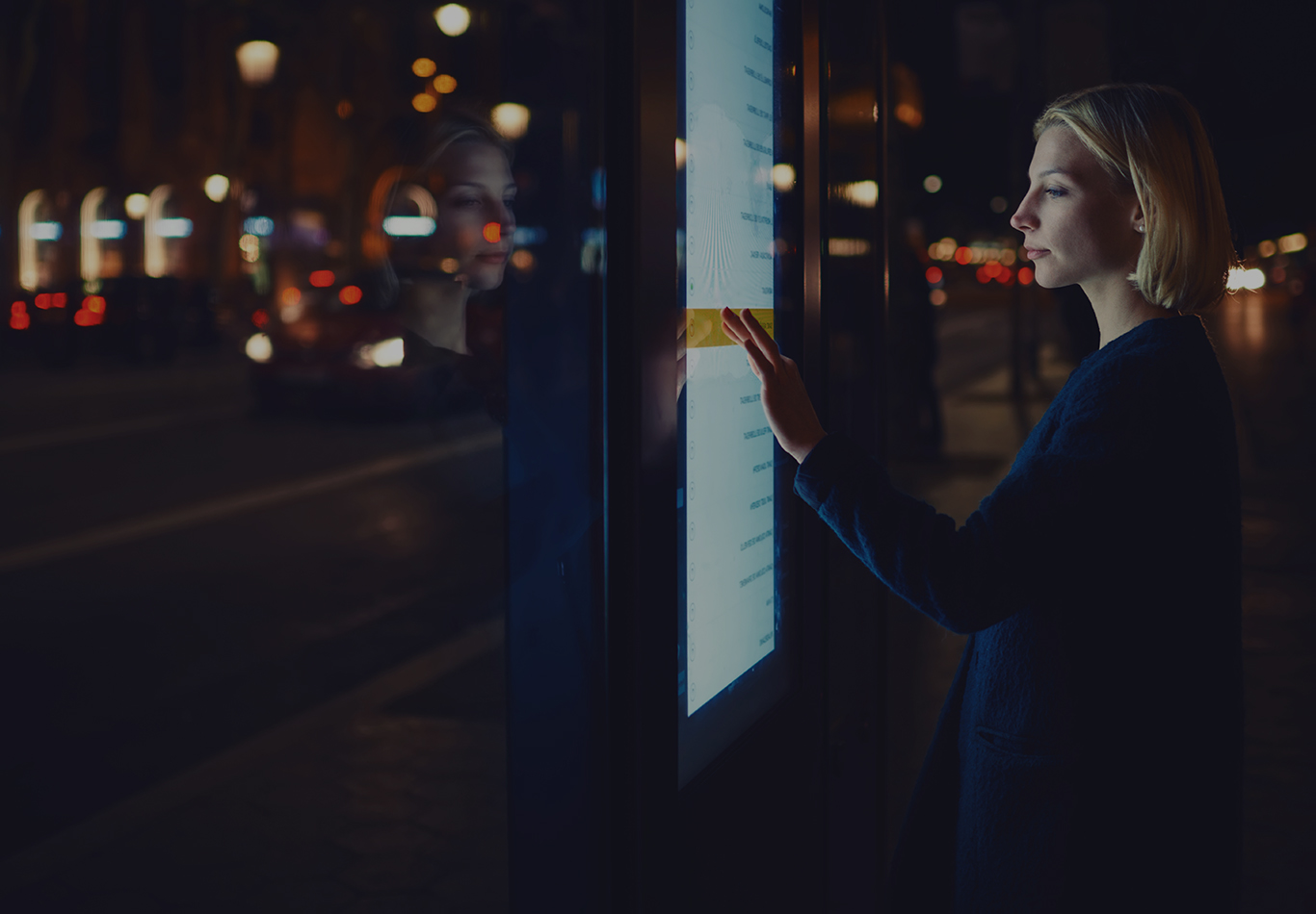 A woman is interacting with a public touch screen at night