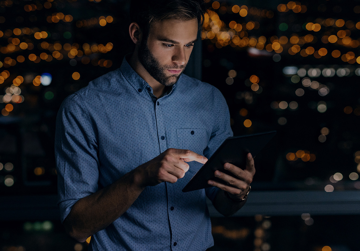A man with facial hair is looking at a tablet at night
