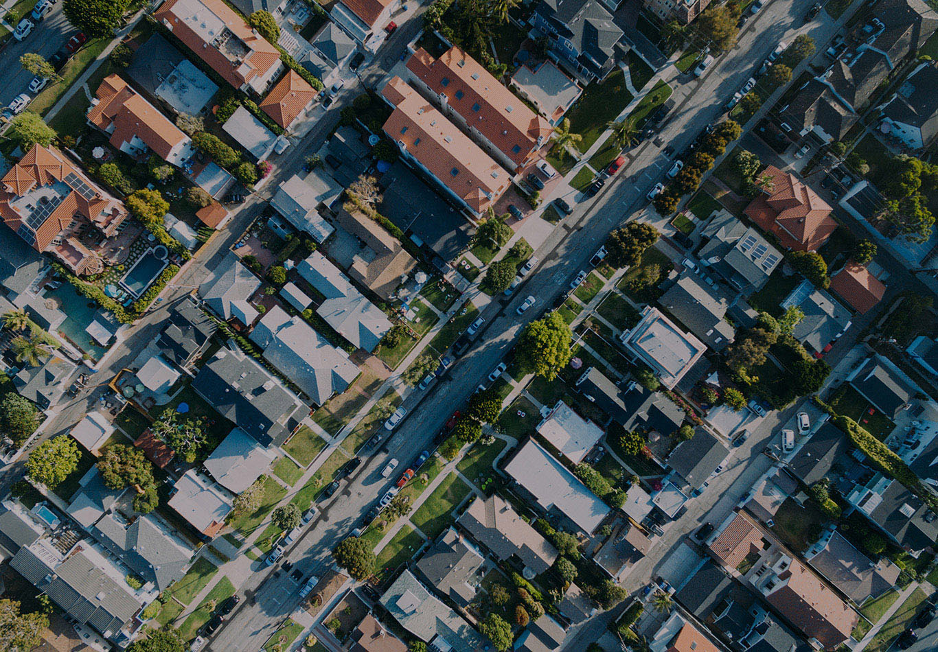 Aerial view of a neighborhood. There are a multiple cars in the street