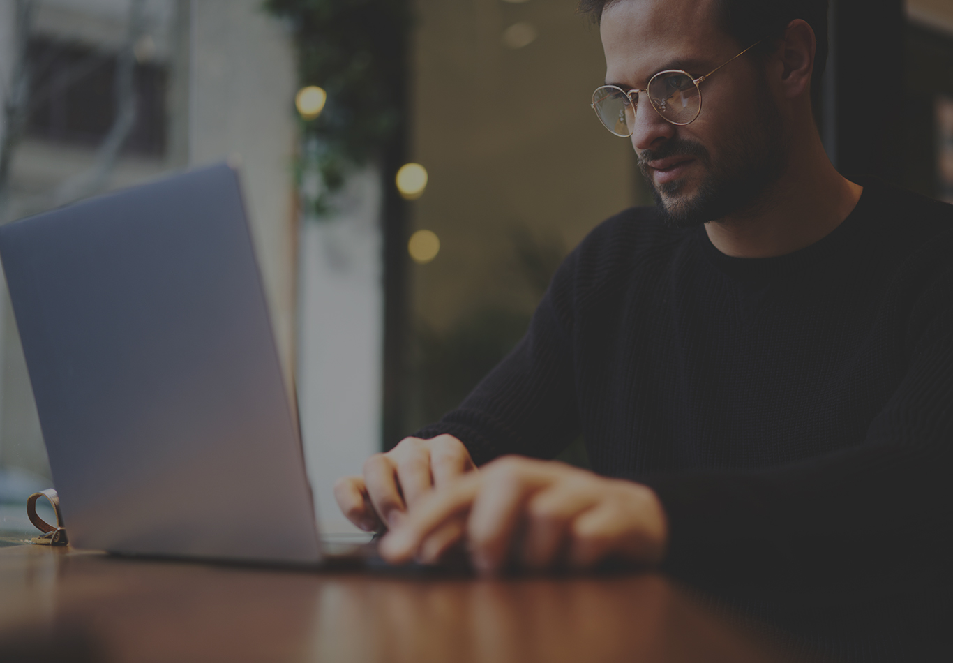 A bearded man wearing circular glasses is working on a laptop