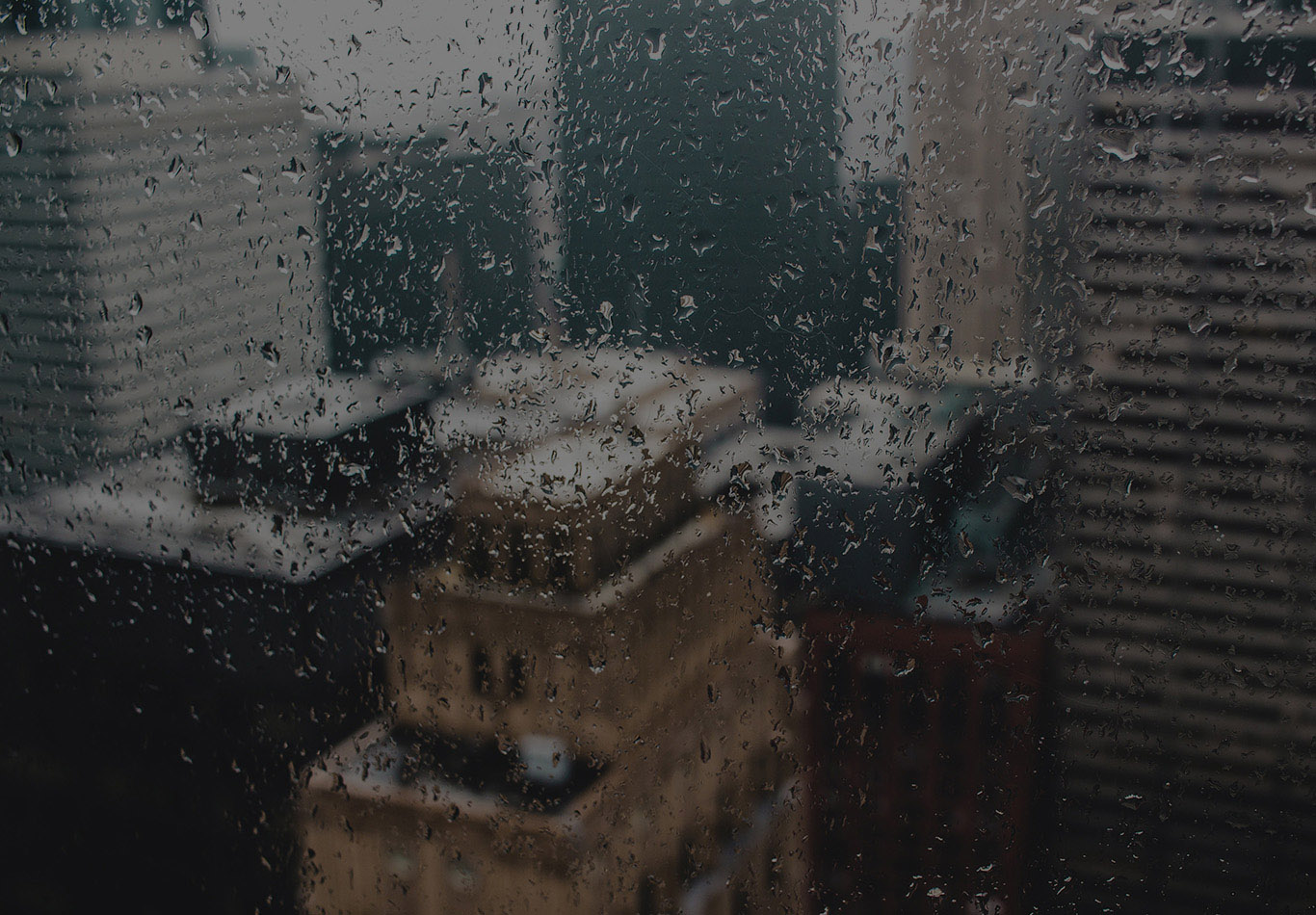 A window with some rain drops on it with some buildings out of focus in the background.