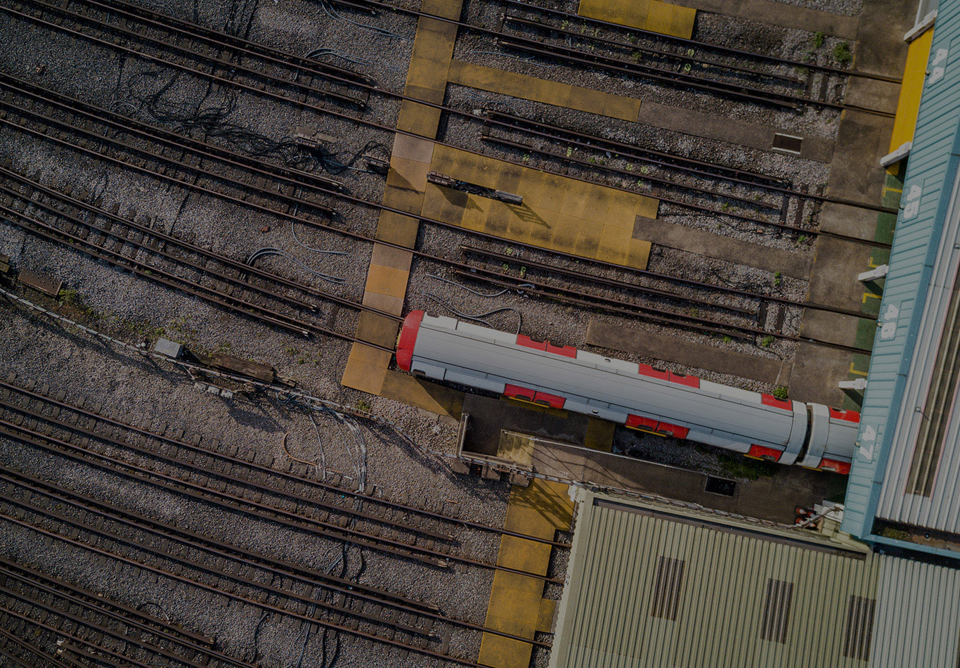 An aerial view of a train depot with one train on the train tracks
