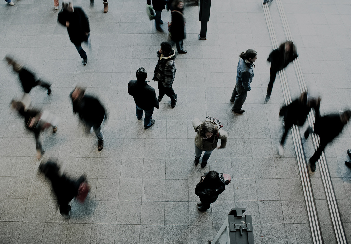 Five in-focus people are walking on a crowded floor