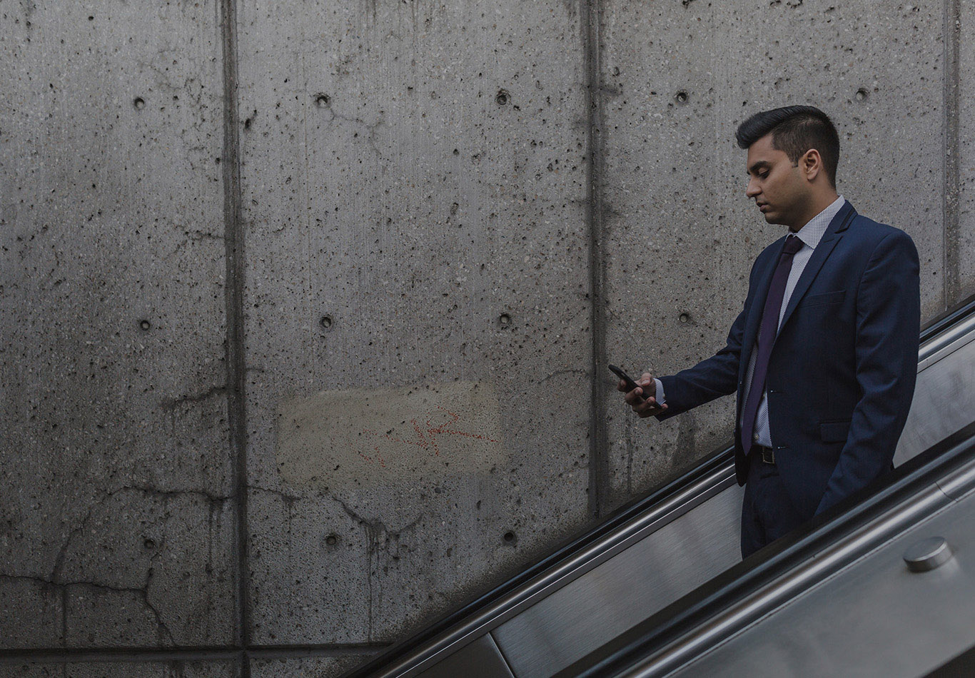 A business man is looking at his phone as they go down an escalator